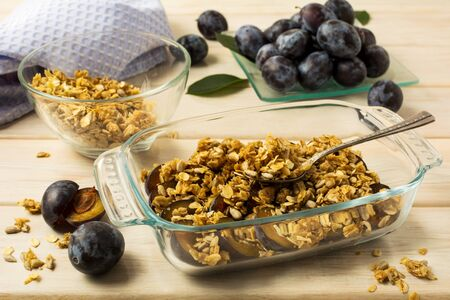 Healthy breakfast fresh plum granola in the glass baking tray