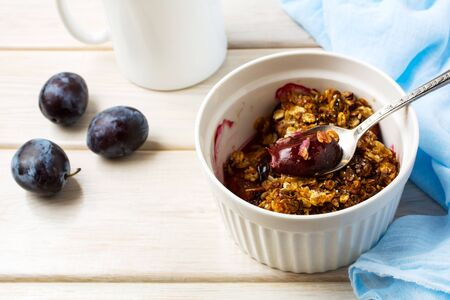 Healthy homemade plum granola in the white baking ceramic form