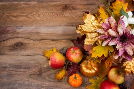 Thanksgiving decoration with golden leaves, pumpkins, apples and purple flowers on the rustic wooden background, copy space