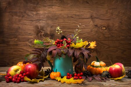 Thanksgiving table centerpiece with turquoise polka dot vase with rowan berries and leaves on the rustic wooden background, copy space