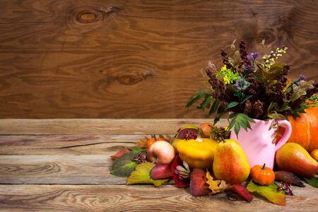 Centrotavola del Ringraziamento con erba selvatica e foglie in vaso rosa su fondo rustico in legno, spazio copia