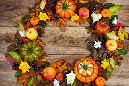 Thanksgiving wreath with pumpkins, apples, colorful fall leaves, pine cones, yellow roses and white flower wreath on the rustic wooden background