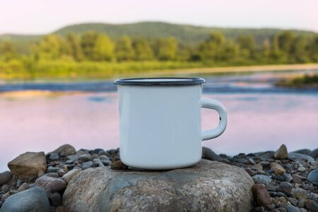 White campfire enamel coffee mug mockup with sunrise river view. Empty mug mock up for design promotion.