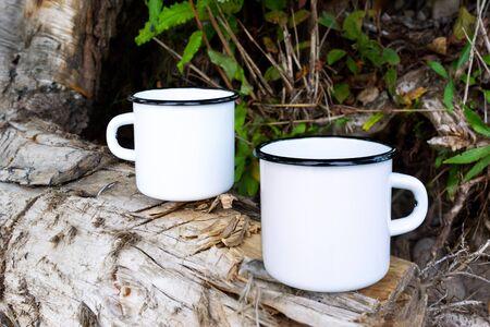 Zwei weiße Lagerfeuer-Emaille-Kaffeebecher-Modell mit altem Baumstumpf. Leere Tasse Mock-up für Design-Werbung.