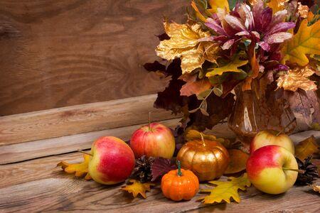 Herbsttischdekoration mit Blättern, lila Blüten, goldenem Kürbis und Äpfeln, Kopierraum
