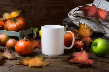 White coffee mug mockup with fall maple leaves, apples and pumpkins. Empty mug mock up for design promotion.