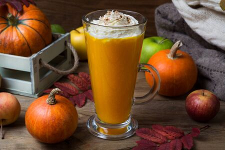 Vegan pumpkin spice coffee latte with whipped cream, leaves and apples on the rustic wooden table 版權商用圖片