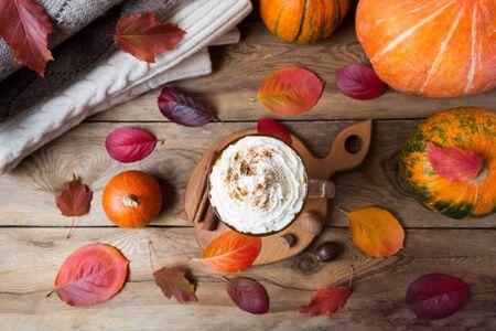 Pumpkin spice coffee latte with whipped cream, cinnamon, nutmeg, fall leaves, wool sweater, top view 版權商用圖片