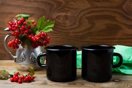 Two black campfire enamel coffee mug mockup with antique jug and cranberry branches.  Empty mug mock up for design promotion. 版權商用圖片 - 136679476