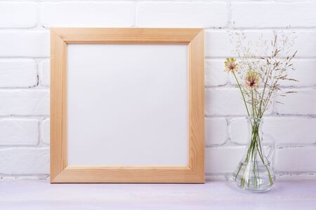 Wooden square picture frame mockup with wild grass in the glass jug. Empty frame mock up for presentation design. Template framing for modern art.