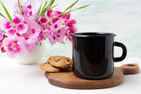 Black campfire enamel coffee mug mockup with cookies and pink godetia clarkia flowers. Empty mug mock up for design promotion.