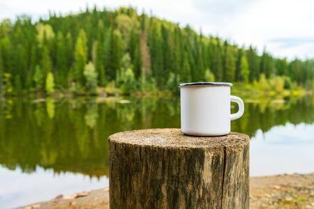 White campfire enamel coffee mug mockup witn the tree stump and river bank view. Empty mug mock up for design promotion.