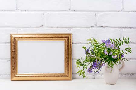 Gold decorated landscape, frame mockup with purple bird vetch flowers in the pitcher vase. Empty frame mock up for presentation artwork. Template framing for modern art.