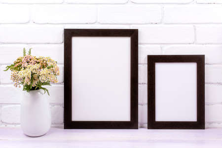 Two black brown frames mockup with pink yarrow wildflowers in the vase. Empty poster frame mock up for presentation design. Template framing for modern art.
