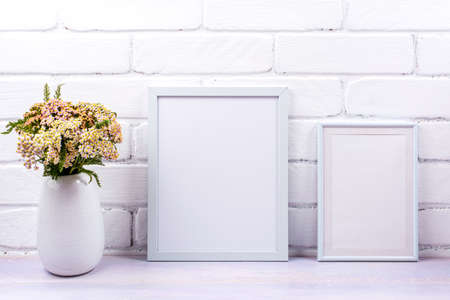 Two white frames mockup with pink yarrow wildflowers in the vase. Empty poster frame mock up for presentation design. Template framing for modern art.