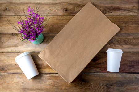 Brown paper shopping bag and two coffee paper cups with lids mockup with purple wildflowers. Kraft recycled grocery shopping bag mock up for branding presentation. 版權商用圖片