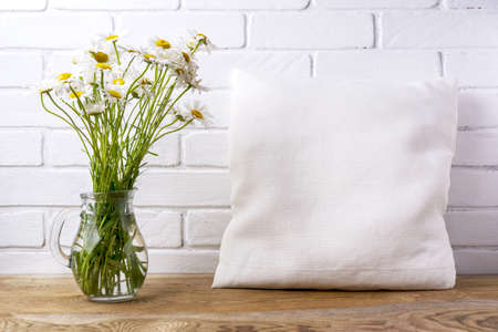 Square cotton pillow mockup with daisy wildflowers in glass pitcher. Rustic linen pillowcase mock up for design presentation