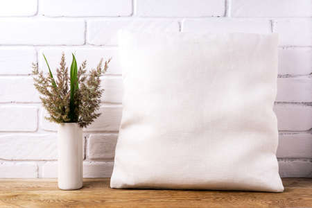 Square cotton pillow mockup with cord grass and green leaves in the vase. Rustic linen pillowcase mock up for design presentation 版權商用圖片