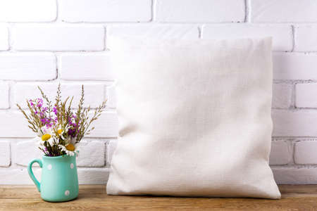 Square cotton pillow mockup with daisy and purple wildflowers in the mint pitcher vase. Rustic linen pillowcase mock up for design presentation