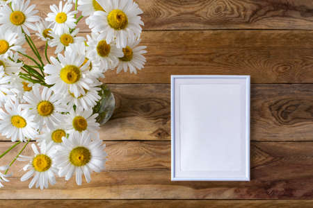 White small frame mockup with daisy wildflowers. Empty frame mock up for presentation artwork. Template framing for modern art.