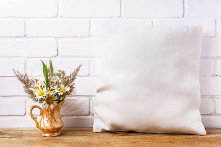 Square cotton pillow mockup with daisy wildflowers and grass in the golden vase. Rustic linen pillowcase mock up for design presentation 版權商用圖片