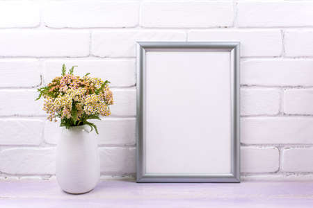 Silver frame mockup with pink yarrow wildflowers in the vase. Empty frame mock up for presentation artwork. Template framing for modern art.