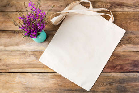 Canvas tote bag mockup with purple wildflowers. Rustic linen shopper bag mock up for branding presentation 版權商用圖片