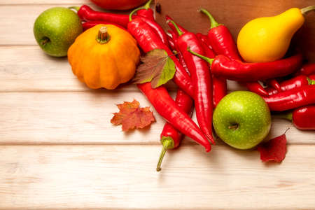 Fall background with yellow pumpkins, red hot chili peppers, green apples and autumn leaves, top view 版權商用圖片