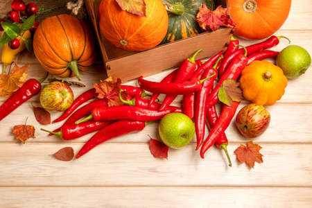 Red hot chili peppers and fall vegetables pumpkins, green apples, cherry and autumn leaves top view