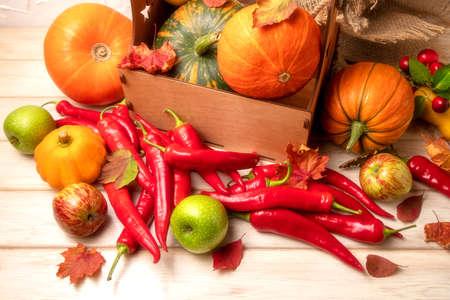 Fall arrangement with burlap, rustic box, pumpkins, squash, red hot chili peppers, apples, autumn leaves 版權商用圖片