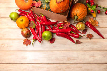 Fall harvest concept with pumpkin, red hot chili peppers, green apples, autumn leaves, chery, top view copy space