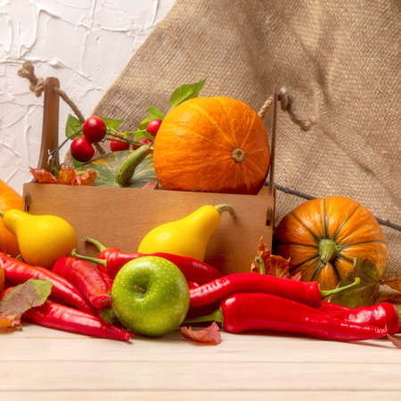 Rustic fall background with wooden box, pumpkin, red hot chili peppers, green apple, cherry and autumn leaves for social media 版權商用圖片