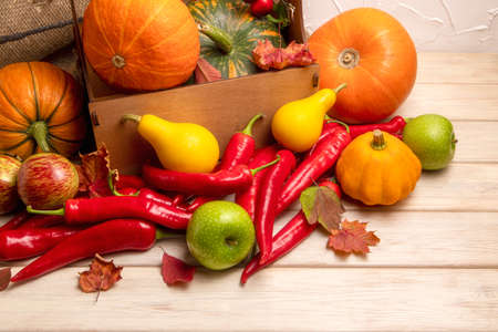 Fall arrangement with pumpkins in the rustic box, red hot chili peppers, green apples, yellow gourds, autumn leaves
