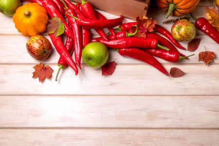 Rustic fall greeting background with red hot chili peppers, green apples and autumn leaves top view, copy space