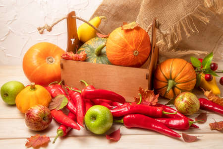 Rustic fall greeting card background with pumpkin in the wooden box, red hot chili peppers, green apples, autumn leaves