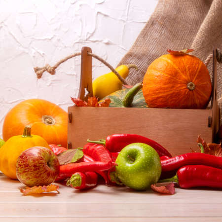 Rustic fall background with wooden box, pumpkin, red hot chili peppers, green apples, autumn leaves for social media