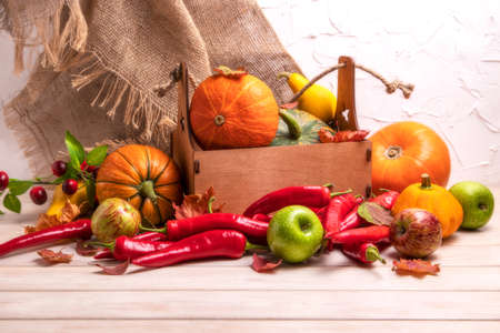 Rustic fall table centerpiece with pumpkin, red hot chili peppers, green apples, autumn leaves and cherry