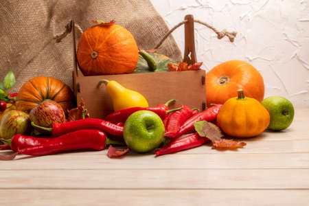 Thanksgiving arrangement with pumpkins and leaves in the rustic wooden box, red hot chili peppers, green apples