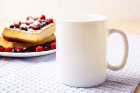 White coffee mug mockup with blueberry waffles and fresh raspberry on the blue checkered napkin. Empty mug mock up for design promotion