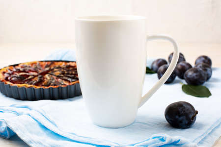 White cappuccino coffee mug mockup with purple plum pie and fresh fruit on the blue napkin. Empty mug mock up for design promotion. 版權商用圖片