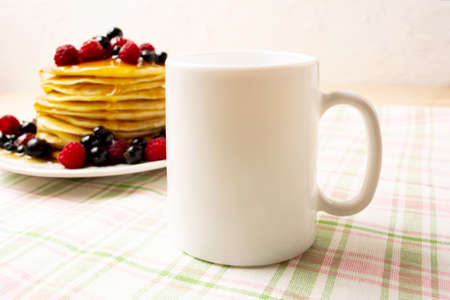White coffee mug mockup with blueberry pancakes and fresh raspberry on the green checkered napkin. Empty mug mock up for design promotion