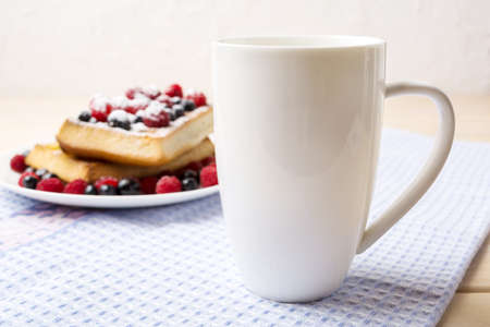 White cappuccino coffee mug mockup with blueberry waffles and fresh raspberry on the blue checkered napkin. Empty mug mock up for design promotion.