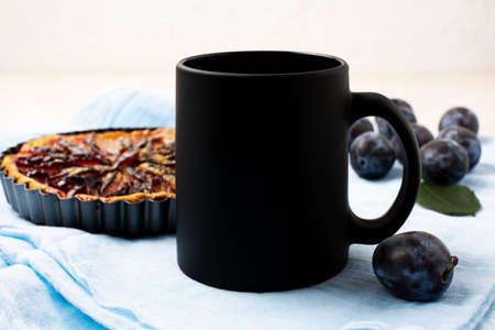 Black coffee mug mockup with purple plum pie and fresh fruit on the blue napkin. Empty mug mock up for design promotion