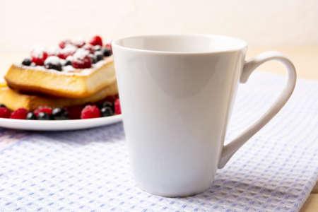White coffee latte mug mockup with blueberry waffles and fresh raspberry on the blue checkered napkin. Empty mug mock up for design promotion.
