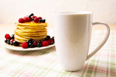 White cappuccino coffee mug mockup with blueberry pancakes and fresh raspberry on the green checkered napkin. Empty mug mock up for design promotion. 版權商用圖片