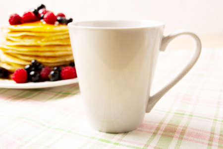 White coffee latte mug mockup with blueberry pancakes and fresh raspberry on the green checkered napkin. Empty mug mock up for design promotion.