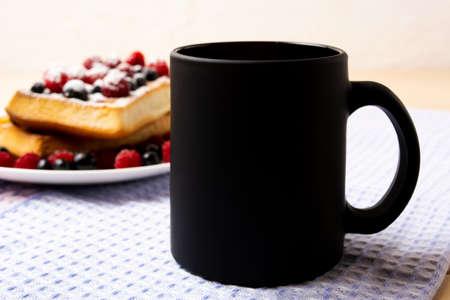 Black coffee mug mockup with blueberry waffles and fresh raspberry on the blue checkered napkin. Empty mug mock up for brand promotion 版權商用圖片