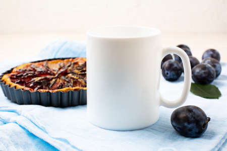 White coffee mug mockup with purple plum pie and fresh fruit on the blue napkin. Empty mug mock up for design promotion 版權商用圖片