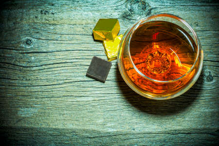 Cognac snifter and chocolate on old wooden background top view. Old fashioned whiskey or scotch glass as loneliness symbol. Unhealthy still life or bad habits concept.