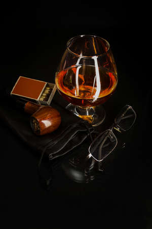 Glass of cognac and smoking pipe. Cognac glass. Brandy glassful. Cognac france. Smoking pipe and scotch drink. Reklamní fotografie